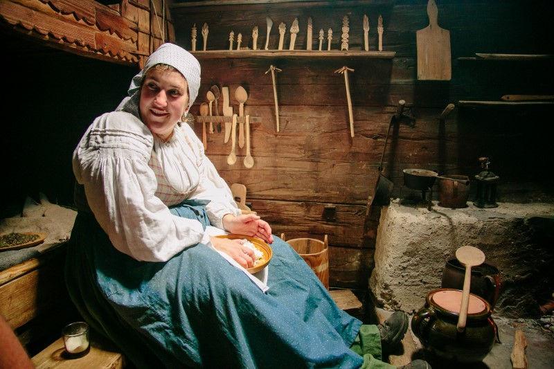 Im Inneren des Museums: Frau in traditioneller Kleidung bei der Herstellung des tradtionellen Kaese. Im Hintergrund sind diverse Kuechenhelfer aus Holz zu sehen.