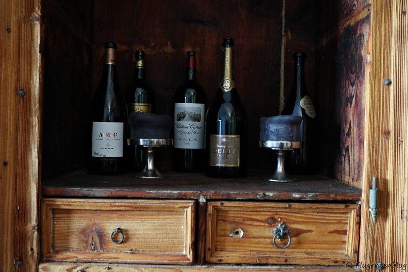 Alte Holzkommode mit Weinflaschen