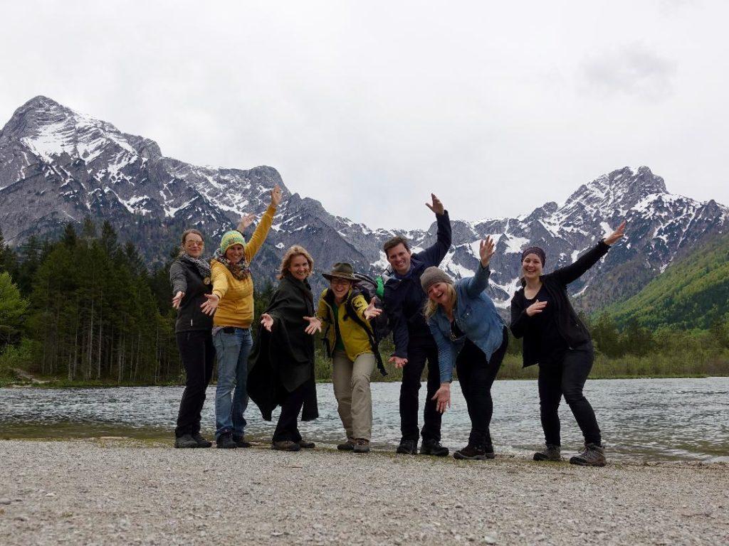 sechs Frauen und 1 Mann stehen beim See, im Hintergrund Berge