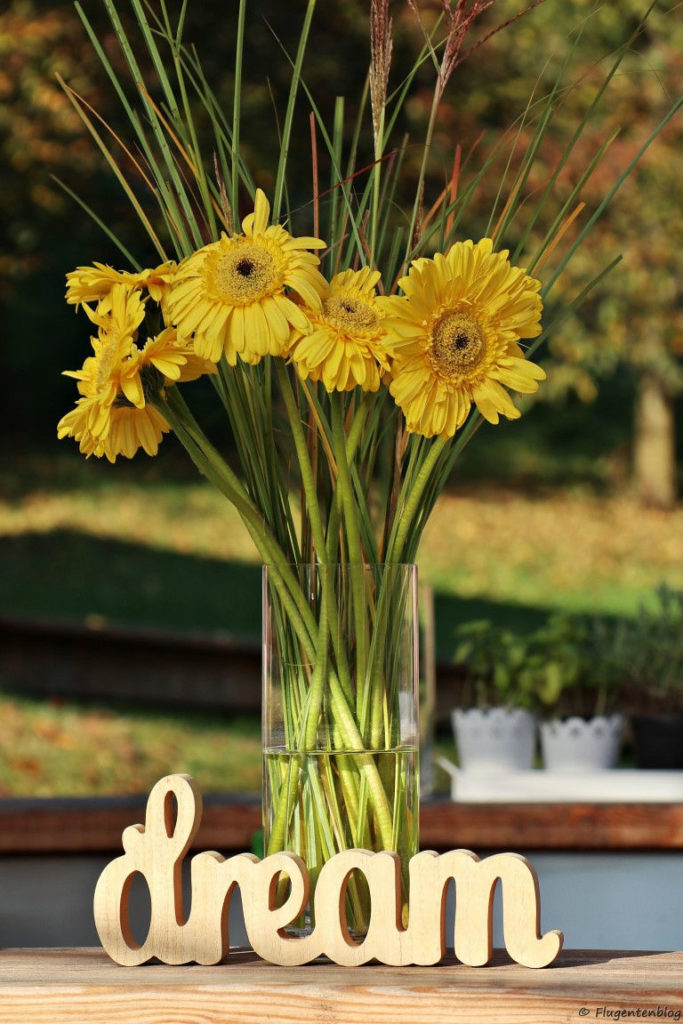 Gelbe Blumen in der Vase und Schriftzug dream aus Holz