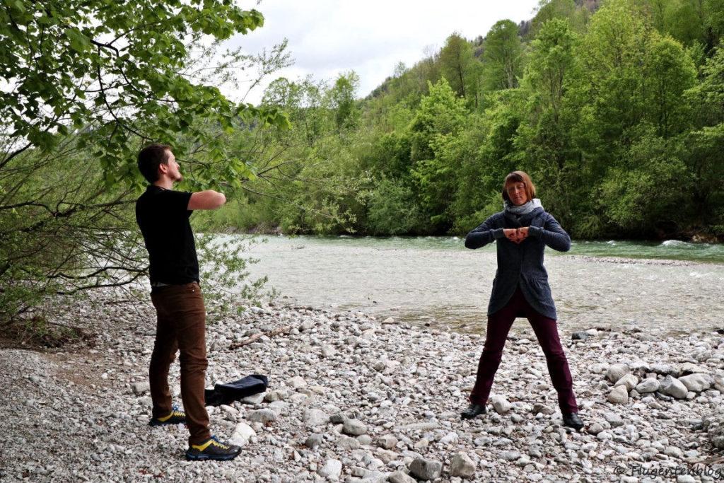 ein Mann und eine Frau stehen an einem Flussbett und praktizieren Wyda