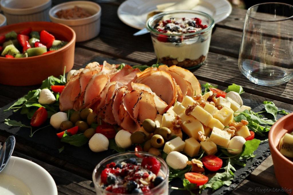 Platte mit Schinken Mozzarellakugeln Kaesewuerfel Cocktailtomaten Ruccola, Joghurt mit Beeren, Schuessel mit Erdbeeren und Kiwi