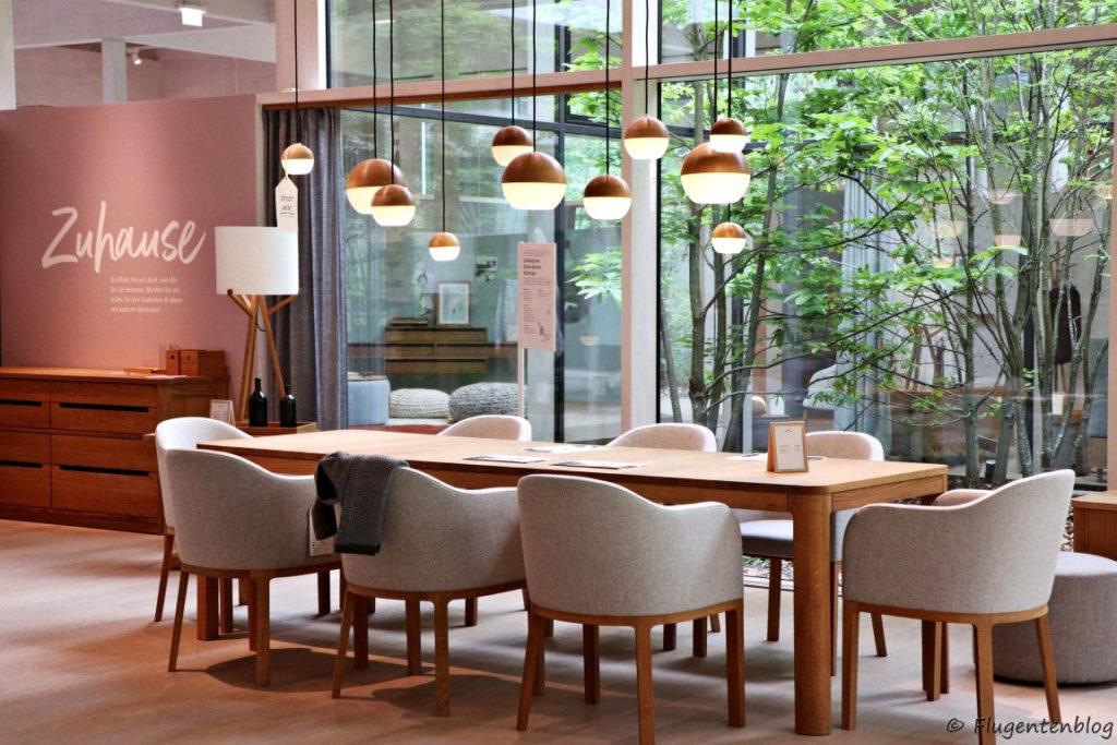 achte hellgraue Stuehle stehen um hellbraunen eckigen Holztisch, weiß-braune kugelfoermige Lampen
