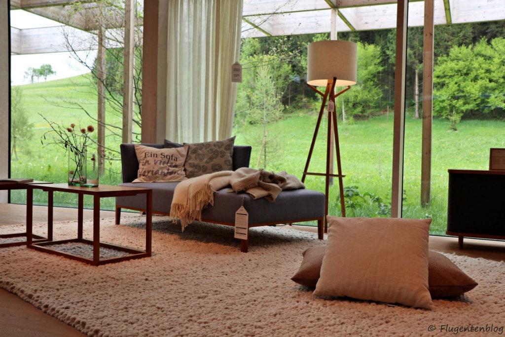 graue Couch mit pastellfarbenen Polster und Decken, Stehlampe, zwei Polster liegen am Boden, heller Teppich, eckiger Couchtisch mit Blumenvase