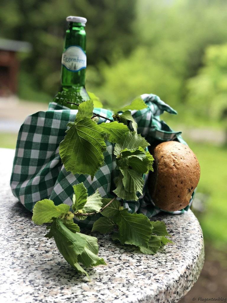 Jausenpaket im gruen weiß karierten Geschirrtuch mit Brot. Blaetterranken, gruene Bierflasche