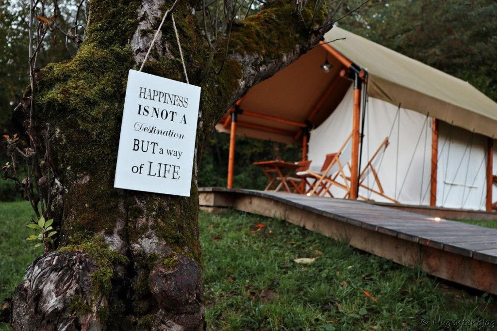 Blick auf die Terrasse vor meinem Zelt mit Holzstuehlen und Holztisch sowie einer Tafel mit der Aufschrift Happiness is not a destination but a way of life