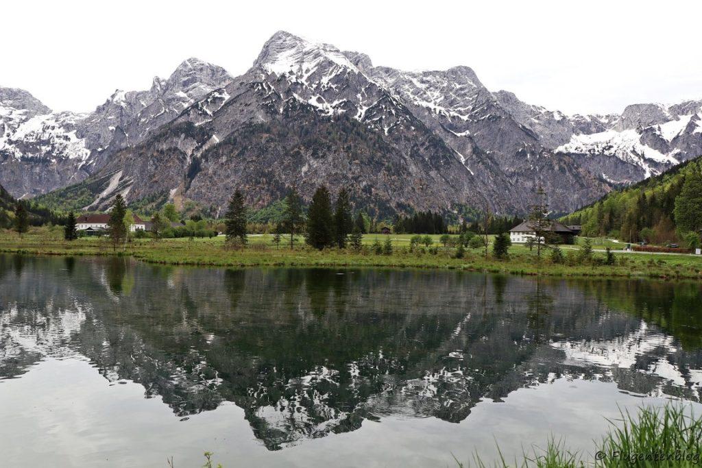 Almsee in welchem sich das schnee bedeckte Hoellengebirge spiegelt