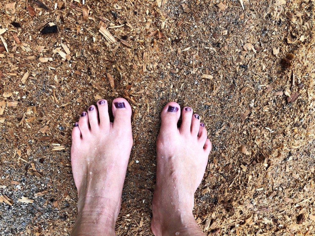 nackte Fuesse mit violett lackierten Zehennaegel stehen auf dem Waldboden