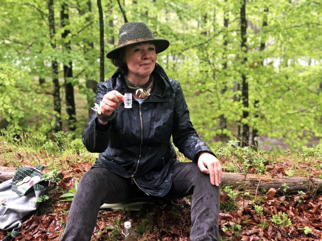 dunkel gekleidete Frau mit Hut sitzt im Wald und hält ein Schnapsglas in der Hand