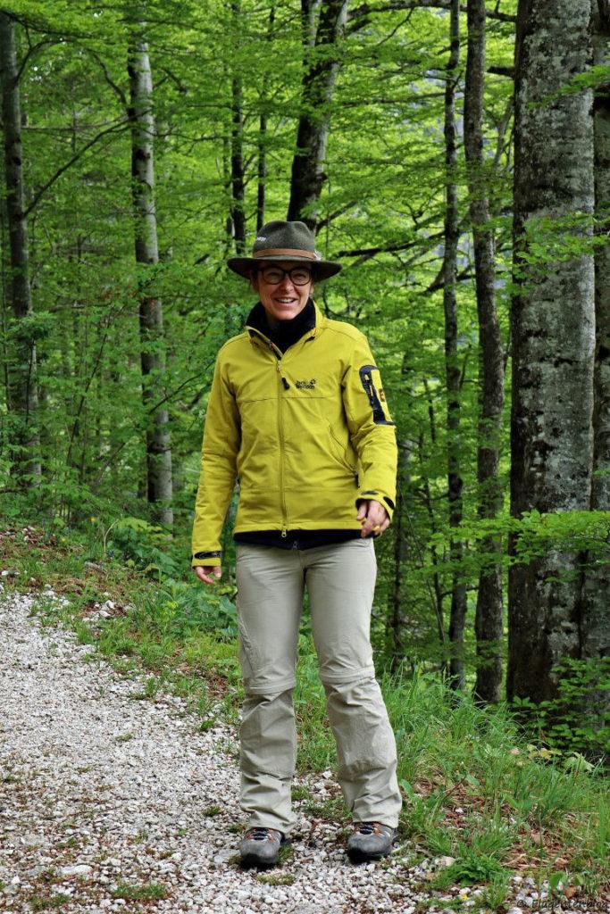 junge Frau mit braunen Haaren, Brille, gelber Jacke und heller Hose steht im Wald und trägt einen Waldness-Hut