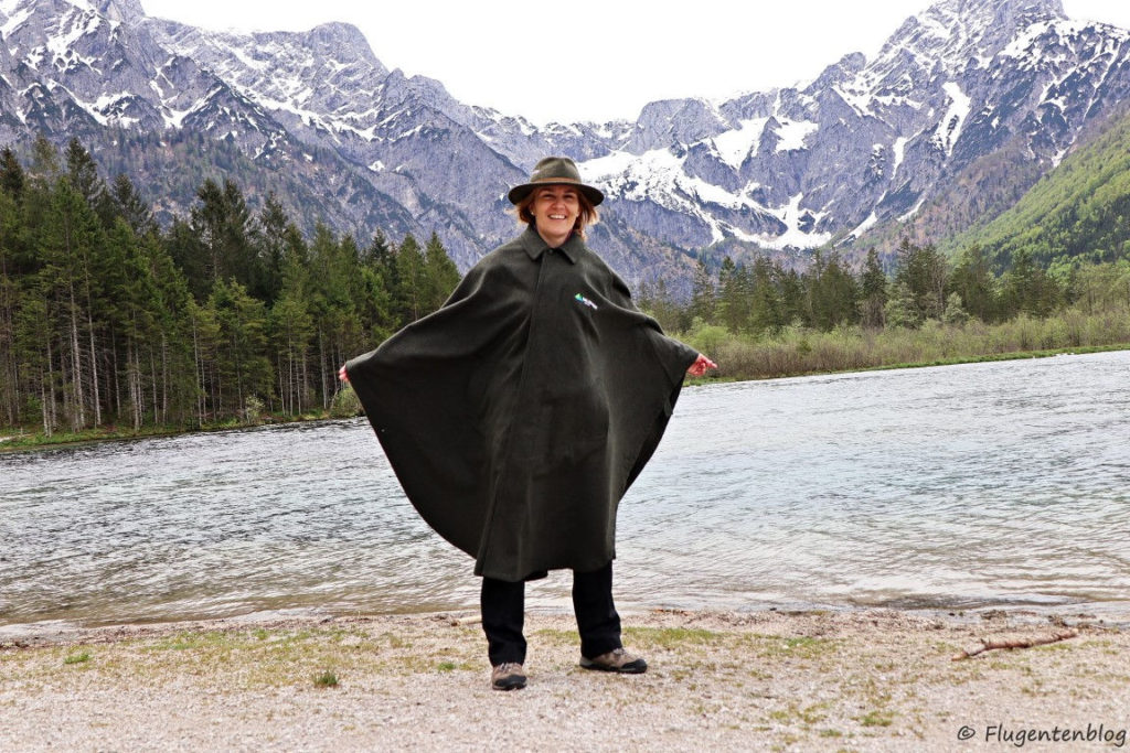 Frau mit braunen Haaren trägt dunkelgruenen Lodenumhang und Waldnesshut. Im Hintergrund der Almsee und verschneite Berge