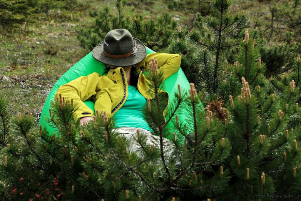 Frau mit Hut auf dem Gesicht liegt im hellgruenen aufgeblasenem Sitzsack und ist von Latschenkiefern umgeben