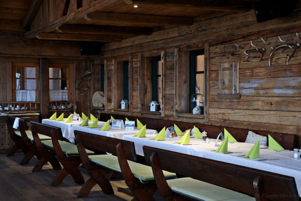 Holzvertafelung an der Wand, Holzbaenke und Holztische mit weißem Tischtuch und gruenen Servietten gedeckt