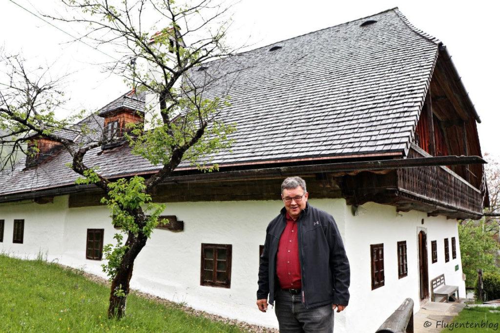 großer staatlicher Mann mit dunklen Haaren und Brille vor weißem Haus mit dunklem Dach und dunkelbraunen Holzfenstern